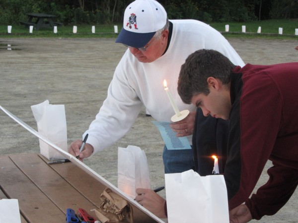 Wayne Sirois (left) and Chad Boucher leave some words on a placard in memory of Lynn Arsenault at a vigil Friday night in Belfast.