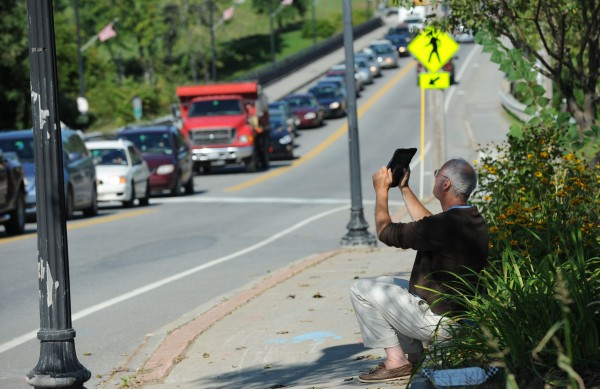 Sam Hunting of Orono snaps pictures of a cottonwood tree being removed to make way for a credit union in Orono on Tuesday. Hunting thinks the tree is an important symbol.