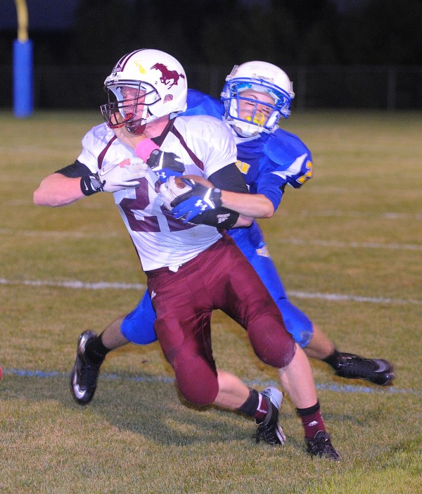 Foxcroft Academy's Peter Boyer (left) scrambles for more yardage as he is tackled by Hermon High School's Matt Farnham  during the first quarter of the game in Hermon Friday night.