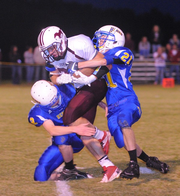 Hermon High School's Matt Farnham (right) and Michael Turner tackle Foxcroft Academy's Corey Bjornson (center) during the first quarter of the game in Hermon Friday night.