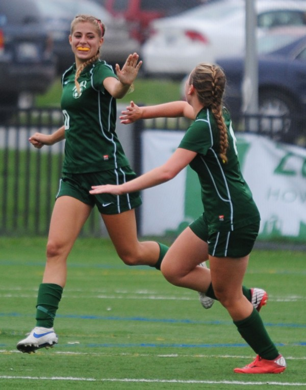 MDI's Opal Curless and Maeve Geary celebrate their goal against Old Town with six seconds remaining in the game at Husson University in Bangor on Tuesday.
