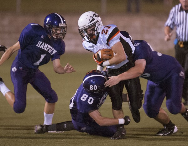 Skowhegan wide receiver Ben Sally (21)  is brought down by Hampden players Robert Frye (1), Jake Black (80), and  Jeremy Kelsey (55) in the first half of their game in Hampden, Maine Friday, Sept. 20,2013. Hampden defeated Skowhegan 32-26.