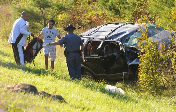 A State Trooper hands a back pack to friends of the victim of a single-car rollover in the southbound lane of Interstate 95 at mile 165 near Etna on Tuesday.