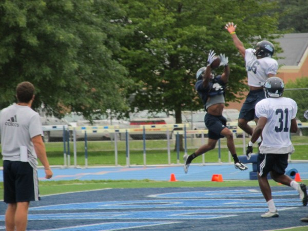 Derrick Johnson of the University of Maine (blue jersey) makes a leaping catch during a recent football practice on Morse Field in Orono.