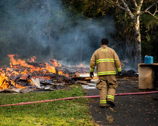 Adam Rider of the Presque Isle Fire Department surveys a fire at 215 Conant Road in Presque Isle on Wednesday. A resident was burning an old shed that then caught a trailer on fire.
