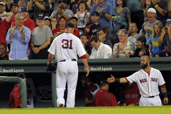 Boston Red Sox starting pitcher Jon Lester (31) is greeted in the dugout by first baseman Mike Napoli after completing the seventh inning against the Detroit Tigers Tuesday night at Fenway Park in Boston.