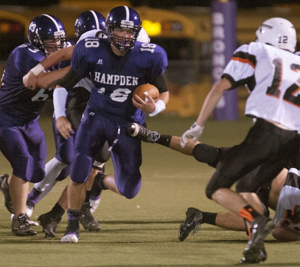 Hampden quarterback Matt Martin (18) looks to get around Skowhegan's Owen Mercier (12) in the first half of their game in Hampden, Maine, Friday night.