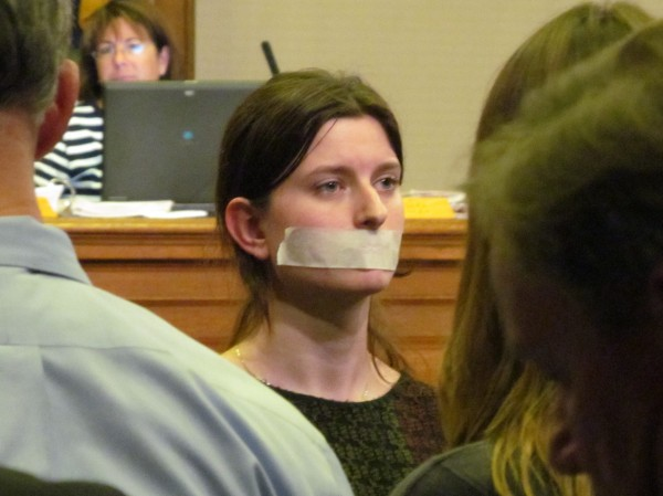 One of three protesters kneels before the audience, back to the City Council, during Monday night's meeting. Two of the demonstrators wore tape over their mouths in part to protest the lack of public input they felt was included in a city deal to sell part of Congress Square park to private developers.