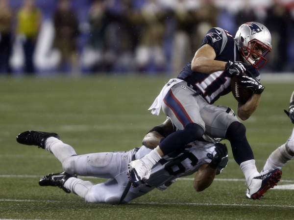 New England Patriots wide receiver Julian Edelman (11) is tackled by New York Jets strong safety Dawan Landry (26) during the second half at Gillette Stadium Thursday night.