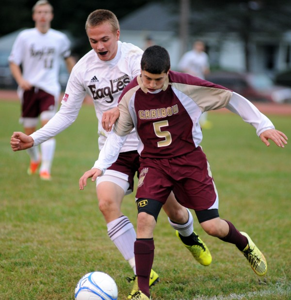Caribou's Michael Hunter and Ellsworth's Jack Weeks go after the ball in Wednesday's game at Ellsworth.