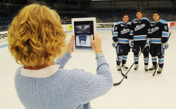 Laura Reid, University of Maine assistant athletic director for public relations, snaps a picture of UMaine hockey players Connor Leen, Andrew Tegeler and Andrew Cerretani during hockey media day at Orono on Monday.