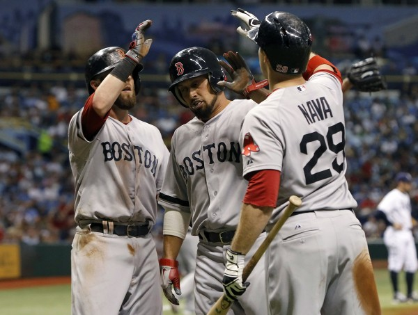 Boston Red Sox right fielder Shane Victorino (18) and second baseman Dustin Pedroia (15) are congratulated by left fielder Daniel Nava (29) at home plate as they score runs during the third inning against the Tampa Bay Rays at Tropicana Field on Wednesday night. Boston won 7-3 in 10 innings.