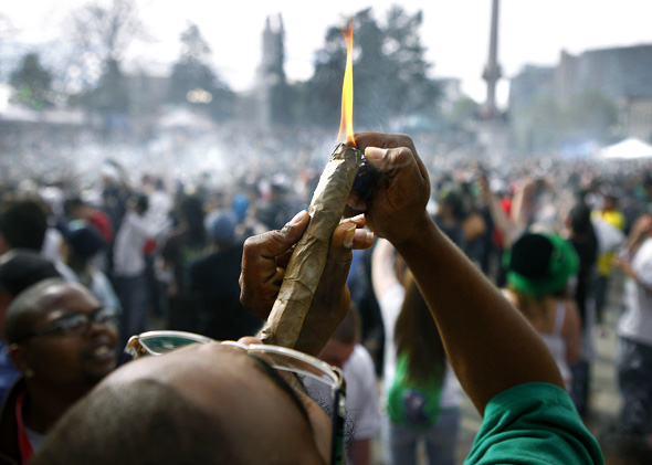 A person identifying himself as Jermagisty Tha King of Denver lights up a 28 ounce blunt at exactly 4:20 p.m. as thousands gathered to celebrate the state's medicinal marijuana laws and collectively light up at 4:20 p.m. in Civic Center Park April 20, 2012 in Denver, Colorado.