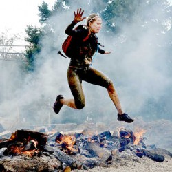 Tracy Bradley jumps over fire during a 13.1 mile obstacle race called the Spartan Beast in Killington, Vt. In 2005, Bradley was one of 15 local high school grads who agreed to let the Sun Journal write about their college experience.