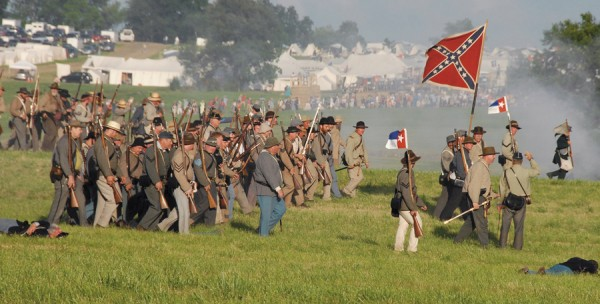 "Confederate troops advance past ""dead"" or ""wounded"" Union soldiers during a battle re-enactment fought at Gettysburg, Penn. on July 4, 2013. During Civil War combat, casualties often vanished behind enemy lines if the other side won a particular fight; a soldier might be captured, killed, or wounded in such circumstances, but if his status remained unknown, his comrades and family considered him ""missing in action."""