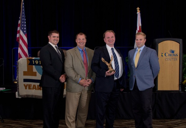 From left are: Cross Insurance Executive Vice President Jonathan Cross; Executive Vice President Brent Cross; President Royce Cross (holding award); and Account Executive Woodrow Cross II.