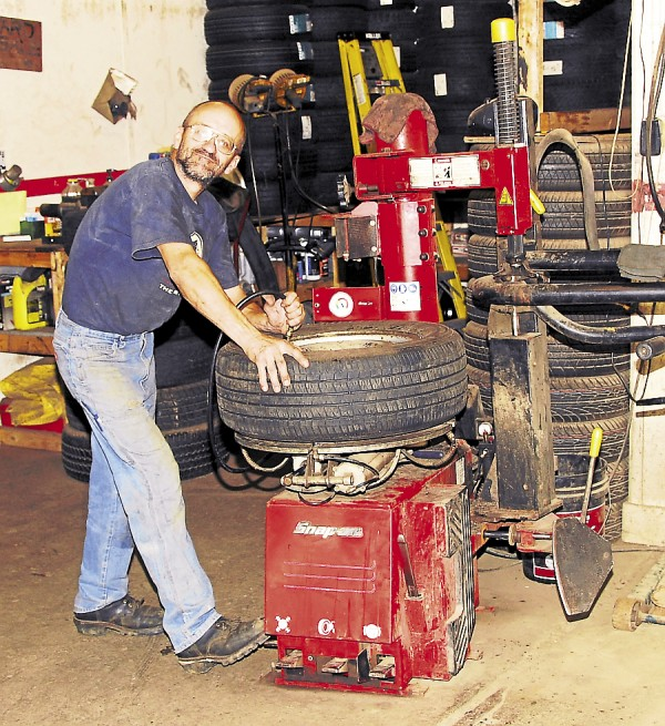 Jeff McLain puts a tire on a rim at Dean's Discount Tire. About 60 percent of tires sold at Dean's are quality used tires. All used tires, although thoroughly inspected before arriving at Dean's, are further tested on a tire machine to detect potential non-visible internal problems.
