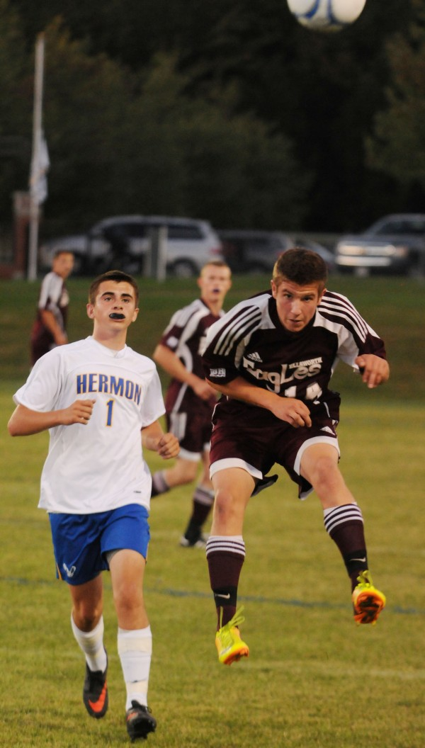 Ellsworth's Ben Haslam heads the ball down the field against Hermon's Aaron Hawes during first half action at Hermon on Thursday.