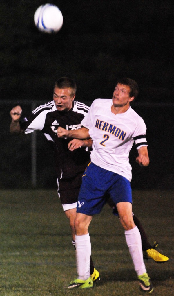 Ellsworth's Jack Weeks heads the ball away from Hermon's Matt Cullens during first-half action at Hermon on Thursday.
