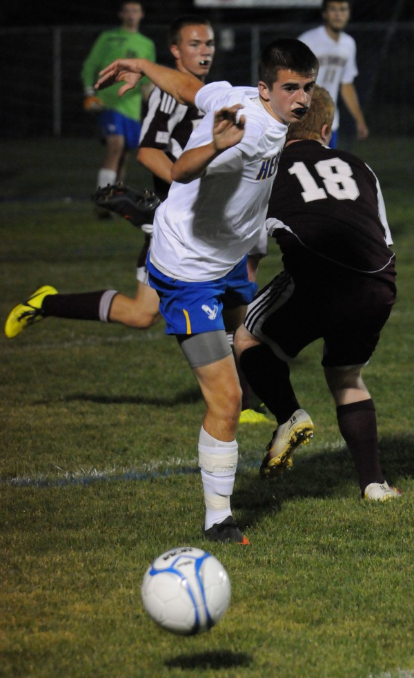 Hermon's Aaron Hawes trips over Ellsworth's Sid St. Peter during first half action at Hermon on Thursday.