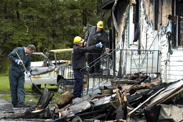 Sgt. Ken Grimes (center) of the Maine State Fire Marshal's Office talks with evidence technicians on Tuesday, Sept. 24, 2013, as they sift through the remains of a house in Island Falls where two people were found dead.