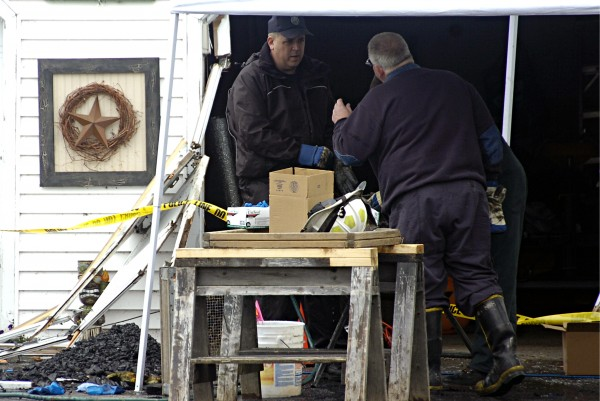 Investigators from the Maine State Fire Marshal's Office sift through remains of a house fire on Tuesday, Sept. 24, 2013 in Oakfield. Two people were found dead in the house of gunshot wounds and a Houlton man was being held as a suspect.