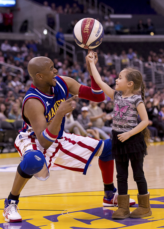 &quotScooter&quot Christensen of the Harlem Globetrotters spins a basketball for the enjoyment of a young fan. As part of the Cross Insurance Center grand opening, the Globetrotters will appear in the arena Sept. 20-21 for two games and for clinics with children.
