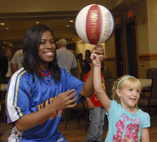 Sophia Morgan of Old Town smiles as Harlem Globetrotter Tammy &quotTNT&quot Brawner balances a rotating basketball on Morgan's right forefinger at the Cross Insurance Center. Morgan met four Globetrotters prior to Sept. 20's game after her parents won a contest sponsored by the Bangor Daily News.