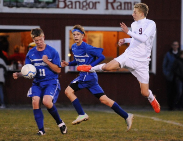 Bangor's Andrew Barrowman (right) kicks the ball past Lawrence's Max Marin (left) and Zachery Peters during first-half action on Tuesday night. Bangor won 5-0.