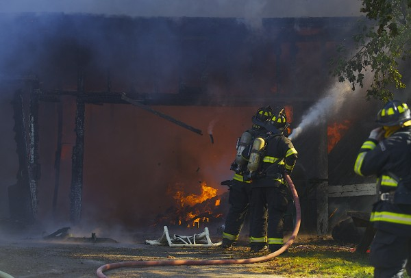 Fire crews fight a fire that destroyed a garage and damaged nearby homes on Hancock Street in Bangor around 2 p.m. Friday afternoon.