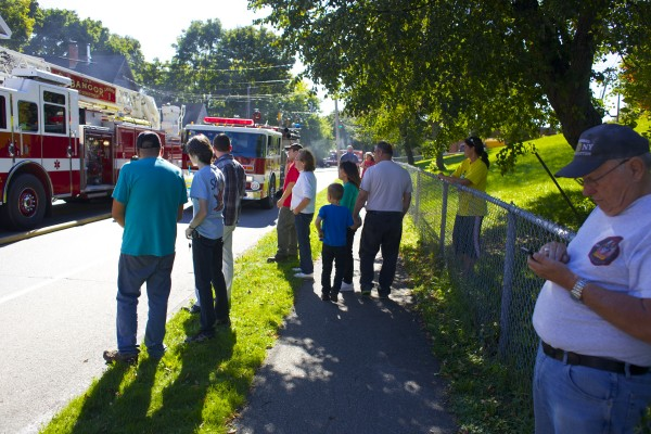 People watch as fire crews fight a fire that destroyed a garage and damaged nearby homes on Hancock Street in Bangor around 2 p.m. Friday afternoon.