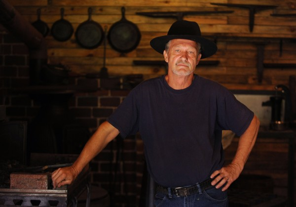 Blacksmith Jerry Gallant stands in the shop he built, at his home in Levant, which includes a hand dug well and train station stove.