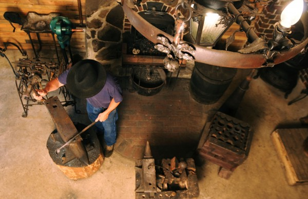 Blacksmith Jerry Gallant hammers a hot piece of steel into a spoon at his shop at his home in Levant.