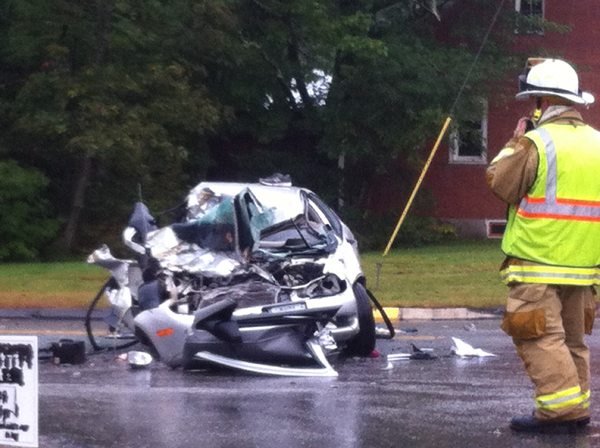 A rescue worker stands by a smashed vehicle that was involved in a three-vehicle collision in Durham on Thursday afternoon.