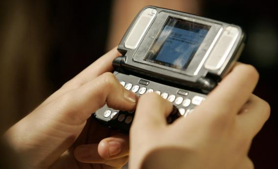 A girl sends a text message on a very old phone.