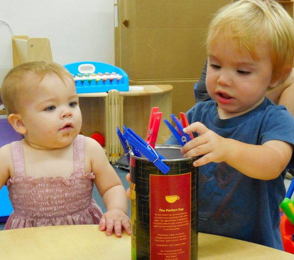 Two children take turns working their small muscles during a fine motor playgroup.