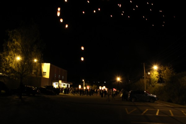 Guests at a reception for Taylor Darveau light several lanterns in the Bucksport High School parking lot. The lanterns floated off into the sky.
