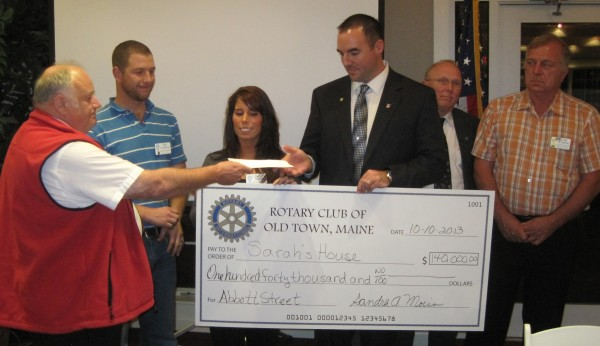 Peter Bosse (left), president of the Old Town Rotary Club, presents a check for $140,000 to Sarah's House of Maine, a hospitality house for cancer payments to be located in the former Fox Run Furniture building on Main Road in Holden.  Accepting the check is Ben Robinson (center), chairman of Sarah's House of Maine and husband of the late Sarah Robinson, who came up with the idea for the hospitality house while receiving treatment for cancer at the Lafayette Family Cancer Center, Eastern Maine Medical Center's Cancer Care of Maine facility in Brewer. The Rotary Club's donation represents the proceeds of the sale of a house that club members built on Abbott Street in Old Town with the help of numerous volunteers and businesses. Also in the photo: Dan Thornton (second from left), president-elect of the Old Town Rotary Club; Lindsay Turner, twin sister of Sarah Robinson and a board member of Sarah's House of Maine; David Walker, who purchased the Abbott Street house; and Stan Peterson of the Old Town Rotary Club, who led the Abbott Street house project.