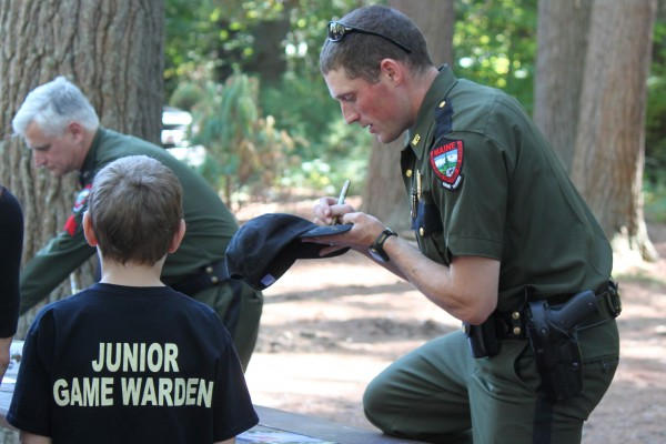 "Maine game warden Kris MacCabe, who stars on the Animal Planet TV show ""North Woods Law,"" signs the hat of 8-year-old Gavin Willett of Monmouth on Sept. 28, ""North Woods Law Day"" at the Maine Wildlife Park in Gray."
