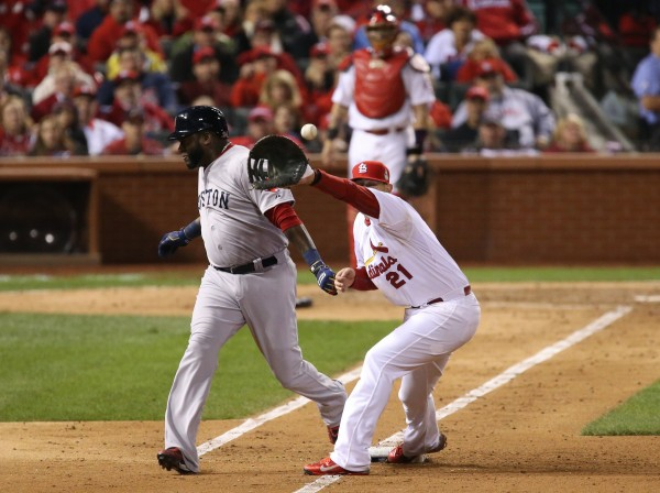 Boston Red Sox's David Ortiz is safe at first as Allen Craig of the St. Louis Cardinals takes the throw in the eighth inning during Game 5 of the World Series at Busch Stadium in St. Louis, Missouri, on Monday, October 28, 2013.