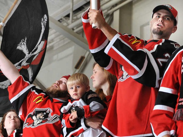 Scott True of Biddeford, right, waves a flag with his wife, second from right holding their son, Weston, as they cheer the Portland Pirates at their home opener against the Manchester Monarchs at the Androscoggin Bank Colisee in Lewiston on Wednesday.