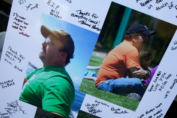 Pictures of Phil Gary, 45, signed by the freshman team, sits on display at a football game in Brunswick Thursday. Gary, a football coach and Boy Scout leader, died unexpectedly on Tuesday leaving eight children and his wife Gail.