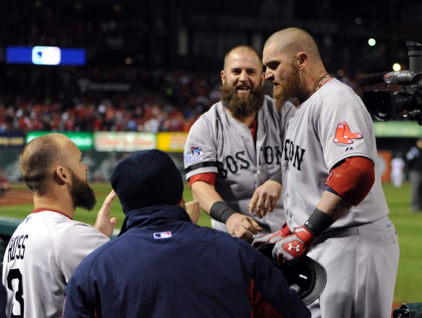 Boston Red Sox left fielder Jonny Gomes (right) is welcomed back to the dugout after hitting a three-run home run against the St. Louis Cardinals in the sixth inning during game four of the MLB baseball World Series at Busch Stadium.