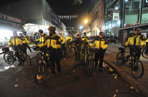 Police with their bicycles move crowds away from Fenway Park after the Boston Red Sox beat the St. Louis Cardinals and win Game 6 of the MLB baseball's World Series in Boston, Massachusetts October 30, 2013.