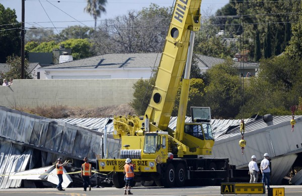 A construction crane is moved into position to remove a hangar from the wreckage of a twin-jet Cessna Citation that crashed into it and caught fire after landing at Santa Monica Airport in Santa Monica, California September 30, 2013. At least three people, including a wealthy California construction executive, were believed killed in the fiery crash-landing of the small jet after a flight from Idaho's Sun Valley resort area, officials said on Monday.