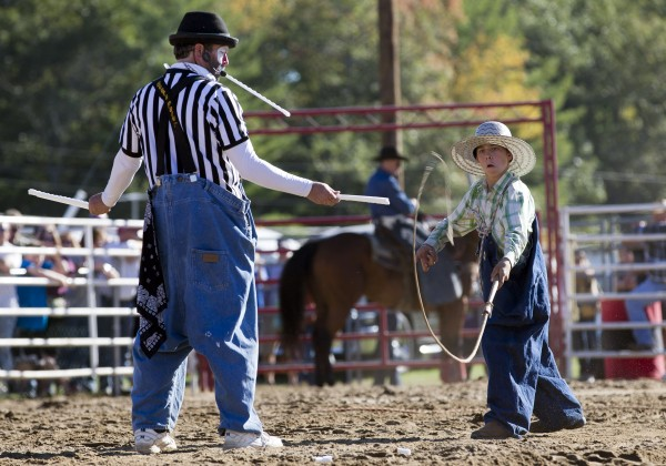 Brinson James, snaps a bull whip to break a target held by his father, rodeo clown Hollywood Harris, while entertaining the crowd in between competitions at the Cumberland County Fair, Saturday, Sept 28, 2013.