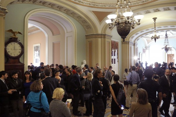 Reporters crowd the U.S. Senate's Ohio Clock hallway after both Republican and Democratic leaders declined to speak after their caucus luncheons in Washington, October 15, 2013. Republicans in the House of Representatives failed to reach internal consensus on Tuesday on how to break an impasse on the federal budget that could soon result in an economically damaging default on the country's debt.