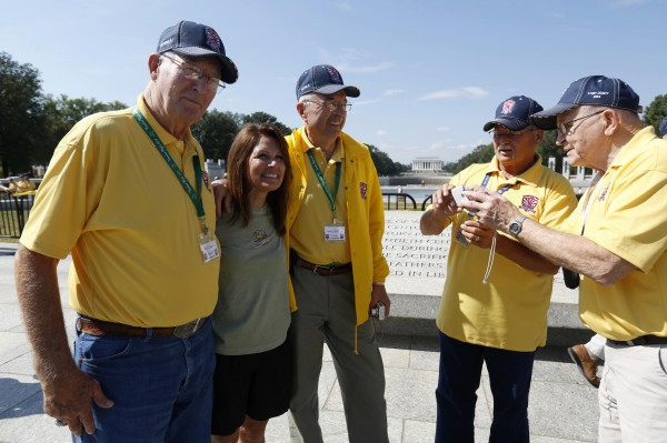 U.S. Representative Michele Bachmann (R-MN) (2nd L) poses for photos with veterans at the World War Two Memorial in Washington October 1, 2013. Despite the U.S. government shutdown affecting the site, a barricade was removed to give veterans accessed the memorial.  Up to one million federal workers were thrown temporarily out of work on Tuesday as the U.S. government partially shut down for the first time in 17 years in a standoff between President Barack Obama and congressional Republicans over healthcare reforms.
