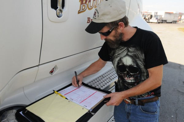 Duane Laybolt of Bridgewater, Nova Scotia, fills in his log book while he awaits his next load at Dysart's Truck Stop in Hermon on Tuesday.