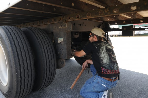 Duane Laybolt of Bridgewater, Nova Scotia, inspects his trailer for loose or low-hanging hoses and wires while he awaits his next load at Dysart's Truck Stop in Hermon on Tuesday.